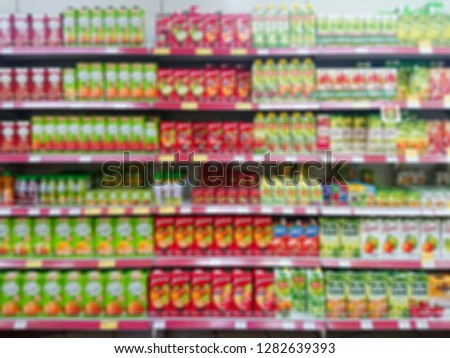 Blurred abstract image. Goods on the shelf of a grocery store. Juices and nectars in cardboard boxes.