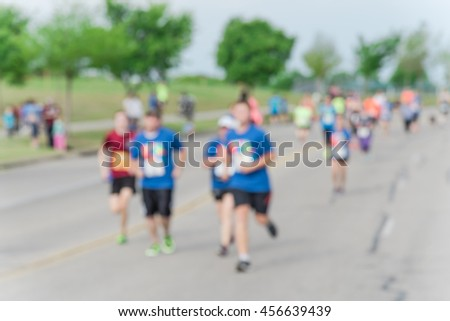 Blurred abstract motion group runners of all abilities of 10K race in Katy, Texas, US. Fitness and healthy lifestyle concept. Athletes on the race. Urban sport event. #456639439