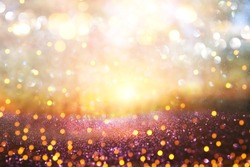 blurred abstract photo of light burst among trees and glitter golden bokeh lights