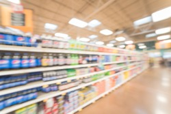 Blurred abstract soft drinks aisle in USA store. Fuzzy drink bottles display on supermarket shelves. The affordability, wide variety of sugary drinks contribute to the growing obesity problem in US