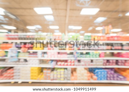 Stock Photo Blurred abstract soft drinks aisle in USA store. Fuzzy drink bottles display on supermarket shelves. The affordability, wide variety of sugary drinks contribute to the growing obesity problem in US