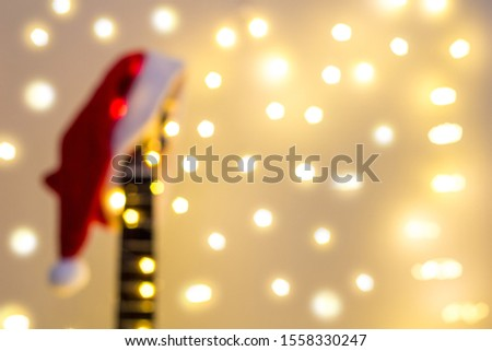 Blurred Acoustic Guitar with red Santa hat and light garland. Christmas music song concept with copyspace for background backdrop