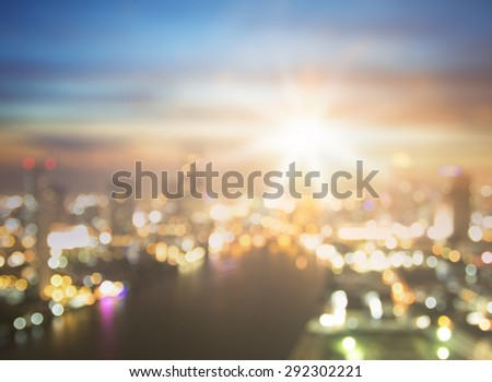 Blurred aerial view of beautiful Bangkok Skyline along Chao Phraya River with Taksin bridge at dusk, Bangkok city, Thailand. Blur amazing light of sunset over city background with bokeh circle light.