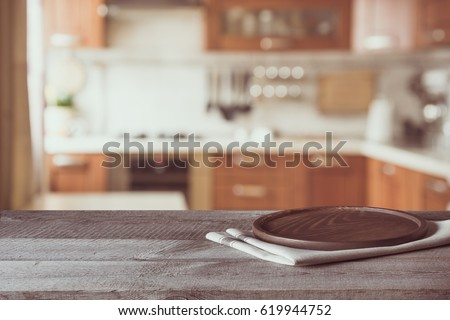 Photo of Blurred and abstract background. Empty wooden tabletop and defocused modern kitchen background for display or montage your products. Toned image.