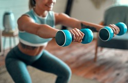 Blurred and cropped image of a beautiful young athletic girl in leggings and top crouches with dumbbells at home. Sport, healthy lifestyle.