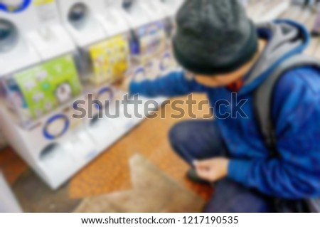 Blurred and out focus of tourist man playing gashapong vending machine in Japan toys shop. Gashapong is one of vending machine dispensed capsule toys,  Popular among tourists visiting Japan.