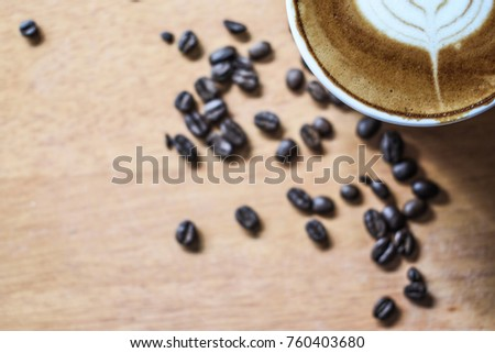 blurred and selective focus of coffee beans and coffee cup on the top right of picture for background #760403680