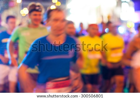 Blurred anonymous crowd of people running on a City Marathon.