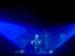 Blurred Asian musician man, drummer playing solo drums on stage with blue light on dark background. Blurry music performance in rock band concert.
