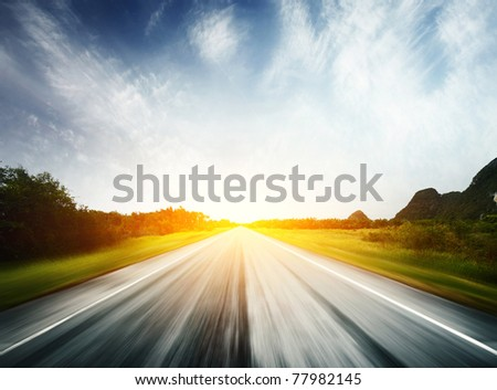 Blurred asphalt road and blue sky with fluffy clouds