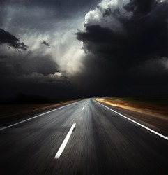 Blurred asphalt road and dark thunder clouds over it