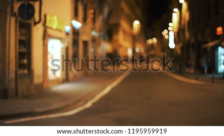 Blurred backdrop of metropolitan city street with lights and buildings #1195959919