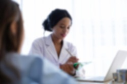 Blurred background. Black African doctor talking to recovering patient in hospital. Sick patient consulting with doctor about medical treatment. Health care insurance & recovering patient concept.
