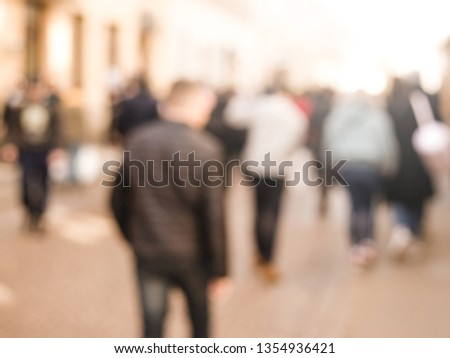 Blurred background. Blurred people walking through a city street. Toned photo. #1354936421