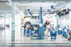 Blurred background : Car technician repairing the car in the shop, garage or service station