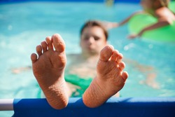 Blurred background, close-up of the feet of children relaxing in the pool in the summer in the backyard. Heat, sun, summer holidays for children, rest and vacations