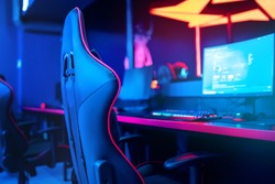 Blurred background computer pc, keyboard armchair, blue and red lights. Concept online eSports arena for gamer playing tournaments.