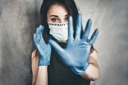 Blurred background. Conspiracy. Beautiful young woman in a white medical mask and blue protective gloves. Woman showing hand stop gesture. Oil paints illustration painting background.