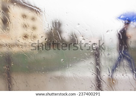 blurred background image with blurred rain drops and man with umbrella hurrying in the rain