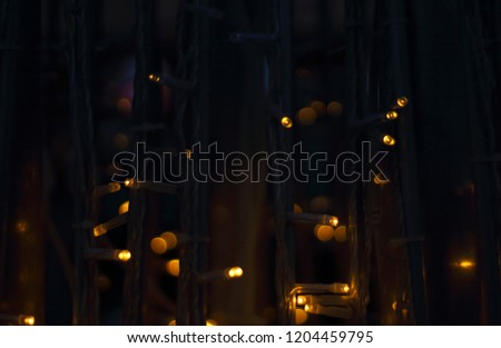 Blurred background in dark tones with glowing LED bulbs holiday garlands emit a warm light with a soft focus and bokeh. Mysterious and cozy background for the New Year and Christmas holidays