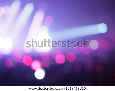 Blurred background light beam of spotlights effect with bokeh defocused lights and silhouette people or audience at live concert in music hall. Enjoy Music Theme or Entertainment Concept. (copy space)
