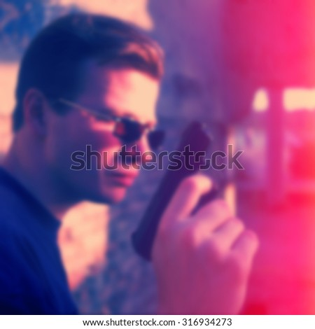 blurred background, man in glasses with a gun outdoors #316934273