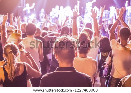 blurred background of a crowd of people standing on a street music platform, in the background a concert of a rock music band #1229483008