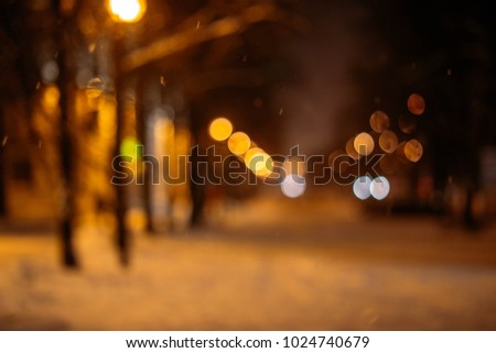 Blurred background of a night snow-covered city street. #1024740679