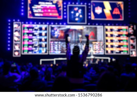 Blurred background of an esports event - Fan on a tribune at tournament's arena with hands raised. #1536790286