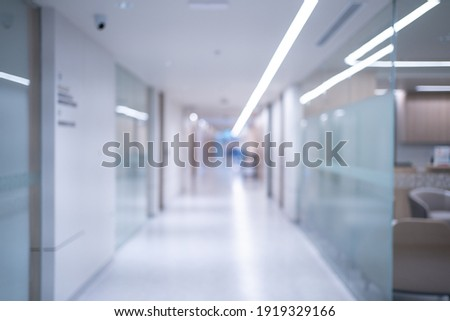 Blurred background of an interior of a modern hospital with an empty long corridor, there are treatment rooms and waiting room for patients and families between the corridor with bright white lights. Foto stock ©
