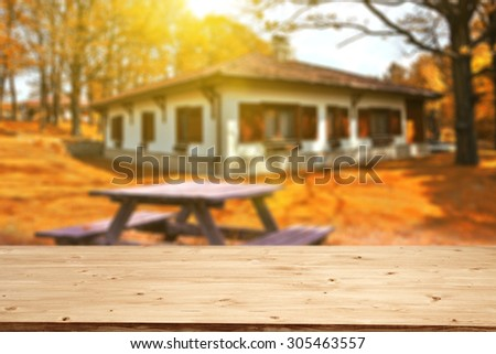 blurred background of autumn and yellow wooden desk space and sun in garden and garden table