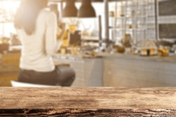 blurred background of bar with woman on chair and brown wooden desk in room of sun light