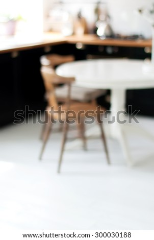 Blurred Background of Black, White Home Kitchen with Light Bokeh. Table and Chair on White Floor