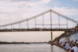 Blurred background of bridge on the sunset. Cityscape captured on the river.