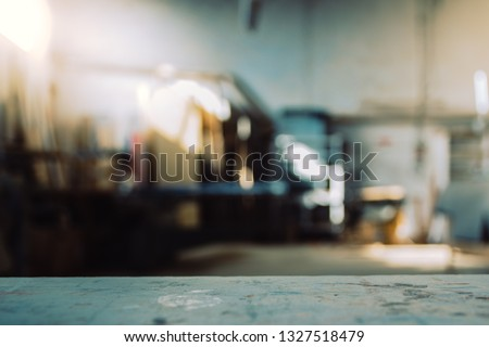Blurred background of carpentry workshop. Machinery background and table scratched stained table top. Copy space. #1327518479