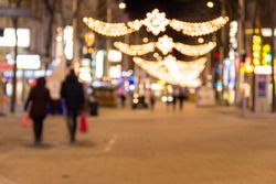 Blurred background of christmas street lights with two people strolling with shopping bags in Vienna, Austria