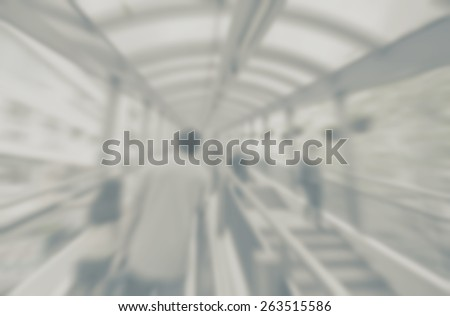 Blurred background of covered walkway with pedestrians. Designed to work with text overlays including the text colour white. Artistic intent with filters and desaturation.