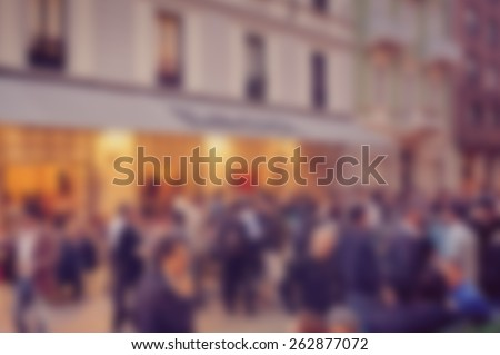 Blurred background of crowds in street outside cafe. Designed to work with text overlays including the text colour white. Artistic intent with filters and desaturation.