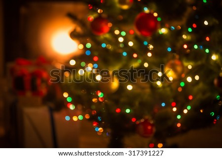 Blurred background of decorated glowing Christmas tree and fireplace stock photo