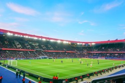 Blurred background of football players playing and soccer fans in match day on beautiful green field with sport light at the stadium. Sports,Athlete,People Concept.Parc des princes,Paris saint german.
