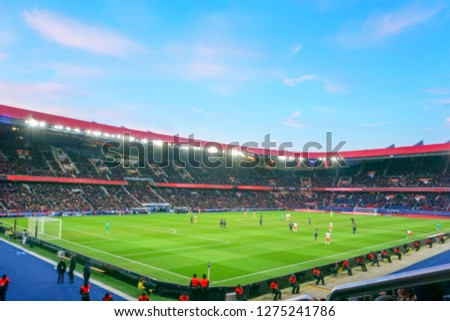 Blurred background of football players playing and soccer fans in match day on beautiful green field with sport light at the stadium. Sports,Athlete,People Concept.Parc des princes,Paris saint german. #1275241786