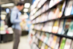 blurred background of man read a book at bookshelves in book store. Student research knowledge in textbook in library of university