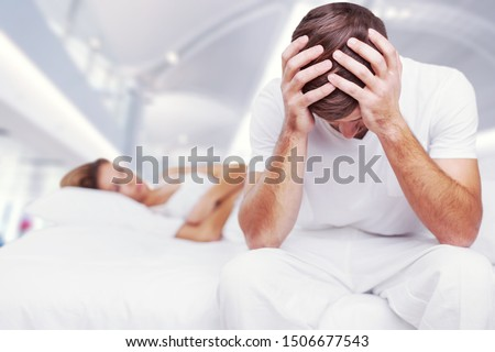 Blurred background of newlyweds have problems fighting in bed. Sleepy married couple have such serious health problem as erection & snoring. Wife is sulky & husband has erectile dysfunction. Сток-фото ©