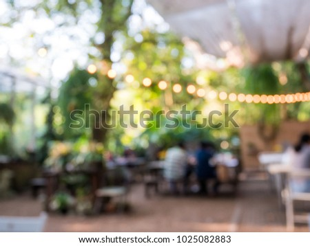 Blurred background of outdoor restaurant with abstract bokeh light. #1025082883