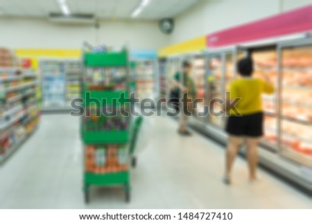 Blurred background of supermarket, people are select products to consume. Concept of spending ,consumption and economic
