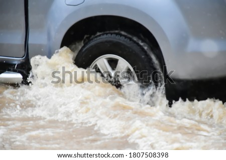 Blurred background of the front wheel of the pickup car which draining floodwater out of the wheel and passing the road which fulled of floodwater in heavy raining day because of the Hegos Storm Stock fotó ©