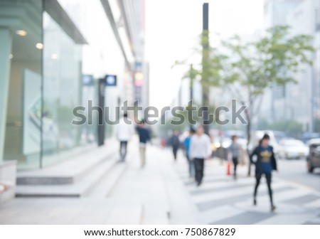 Blurred background of traffic on the road and people walking on sidewalk, business area in city, Seoul Korea, perspective.