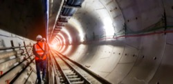 Blurred background of underground tunnel construction with light at the end of the tunnel.Transport pipeline by Tunnel Boring Machine for electric train subway with control engineer or security safety