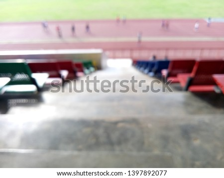 Blurred background of view of stadium with empty seat. Colorful seat in soccer stadium when holiday. Blue, green, red and yellow iron seats. Landscape of free arena seating.   #1397892077