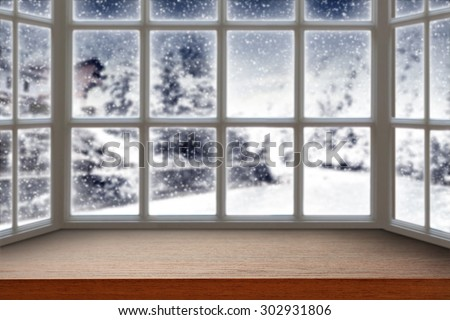 blurred background of window with winter landscape and dark brown furniture top